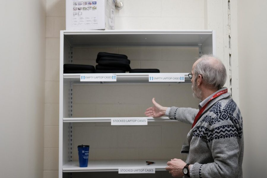 Librarian William Pankey points at empty shelves because Harper students have rented out all of the free available laptops as of February 21st, 2020. Photo by Vicki Land.