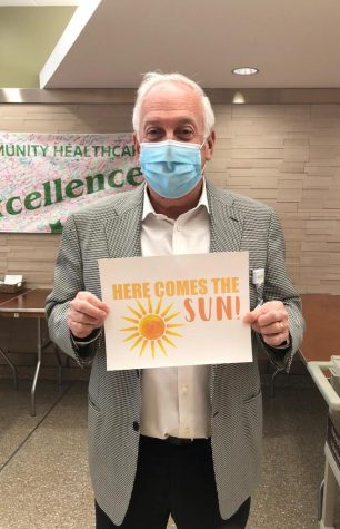 """Dr. Alan Loren holds a Here Comes The Sun"""" sign when a COVID-19 patient is released.  Northwest Community plays the cheerful song over the loudspeaker throughout the hospital to reinforce the hope and joy they value in these tough times. Courtesy of Northwest Community Healthcare and Amy Jo Steinbruecker, Media Relations Manager."""
